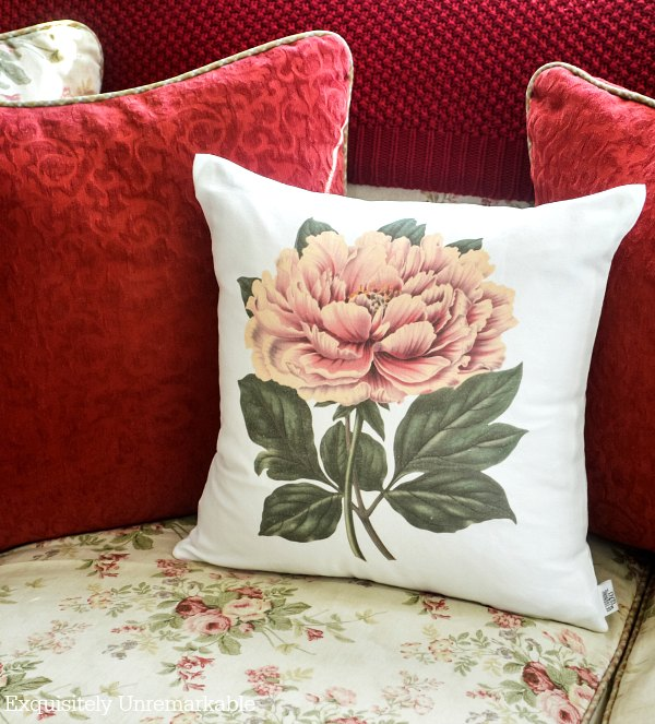 Poppy pillow, red pillows and red throw blanket on a floral couch.