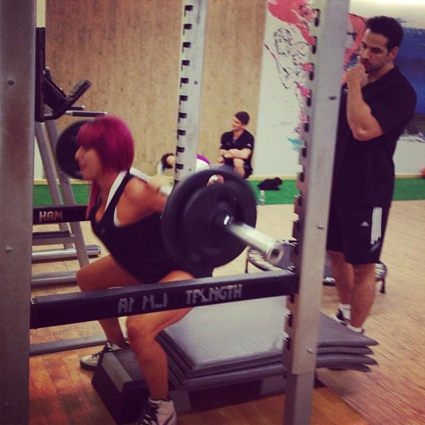 Com supervisão de personal trainer, Thais Bianca faz agachamento com barra livre