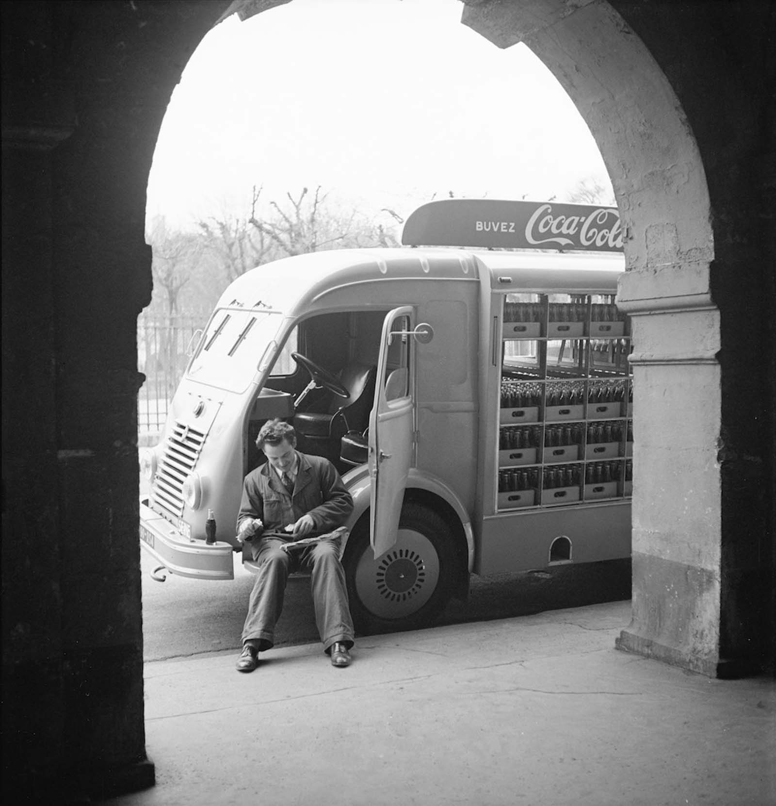 A Coca-Cola delivery driver sits in the open door of his truck while on a break, in France.