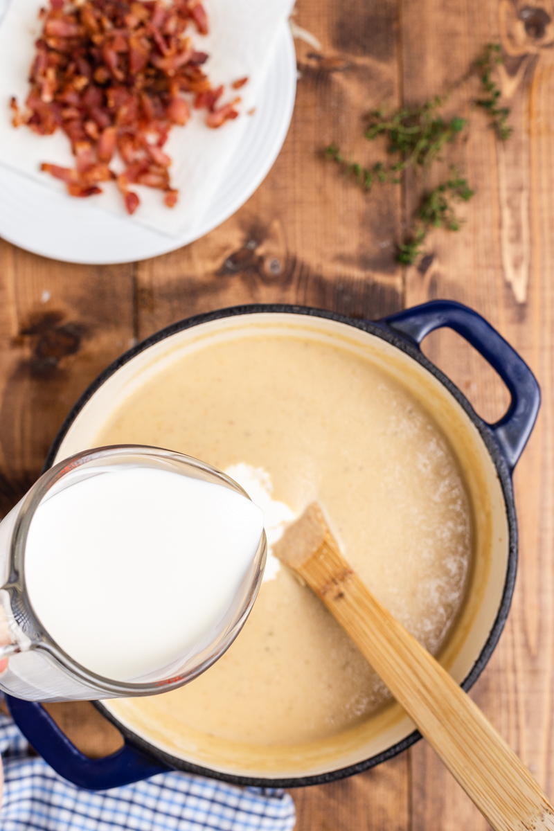Overhead photo of the process of adding heavy cream to Easy Cauliflower Cheese Soup in a large blue soup pot.