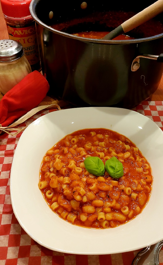 this is Italian pasta fagioli with ditalini and white beans in a tomato red sauce in a white dish