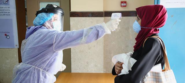 Toman la temperatura de una mujer en un centro de la Franja de Gaza durante la pandemia de COVID-19.UNRWA/Khalil Adwan