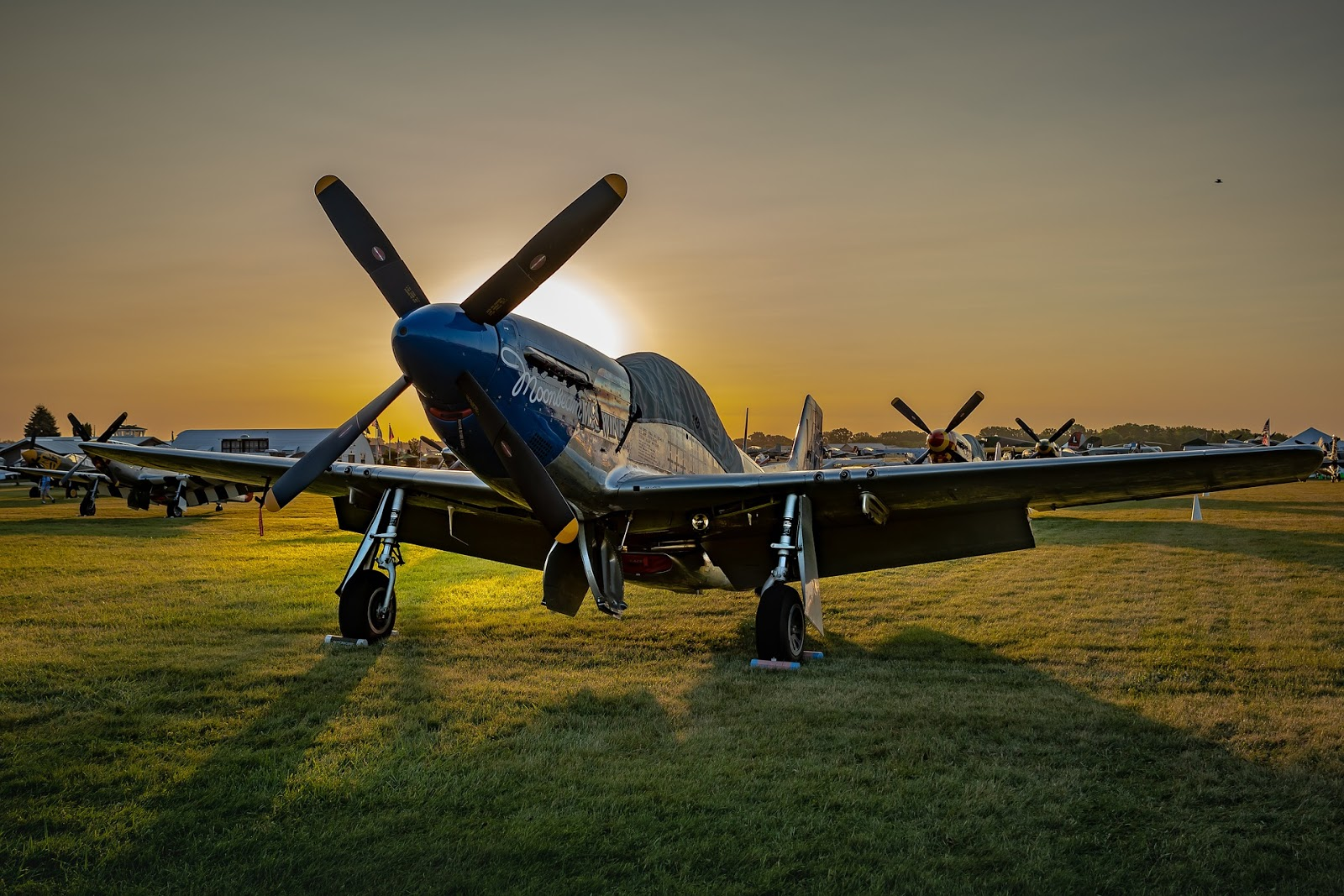 world war 2 fighter plane stands on a grass runway with sunset in background for blog post about air force war movies