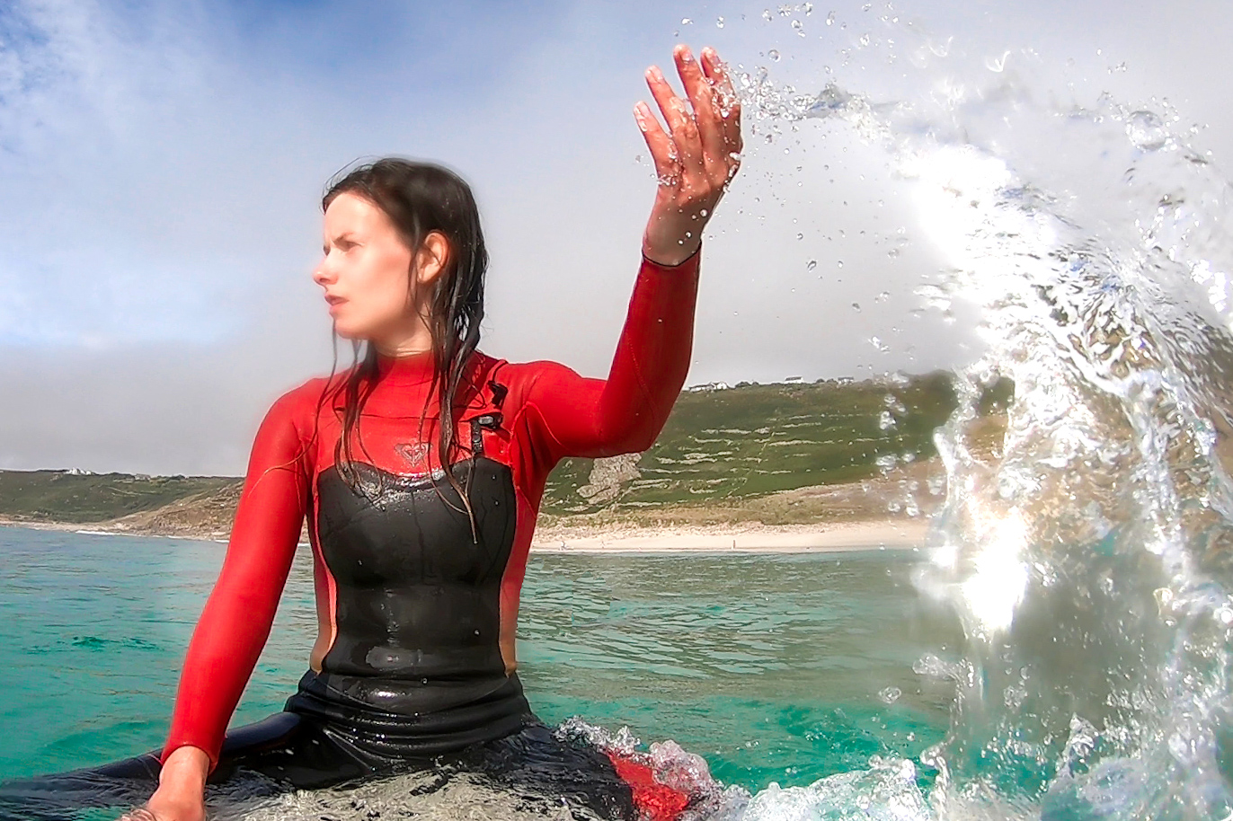 Girl on a surfboard in Cornwall learning how to surf