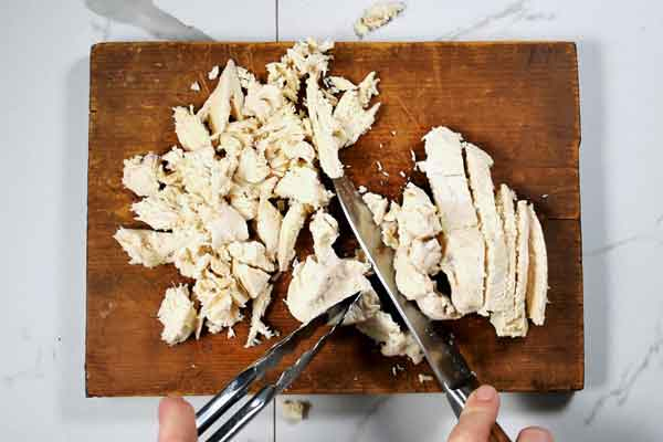 Shredding poached chicken to use in chicken salad recipe