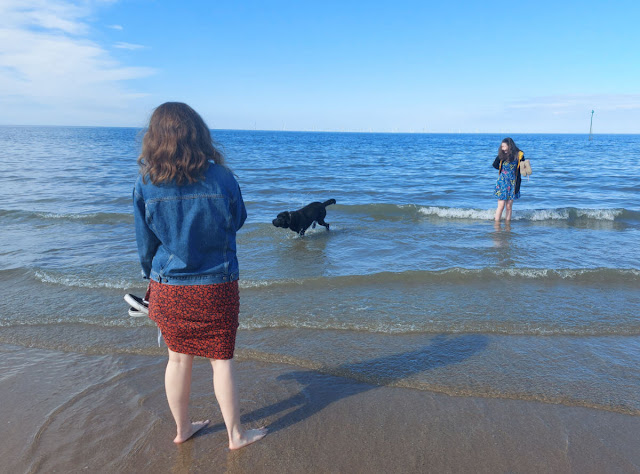 Two girls standing in the sea watching a black dog