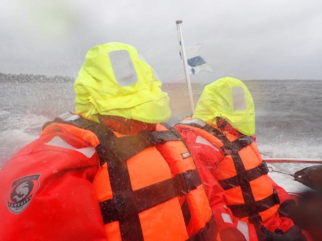 Kaksi henkilöä veneen kyydissä veden pärskyessä pelastautumispuvuissa