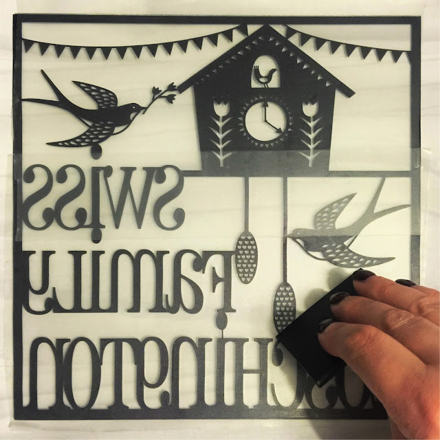 Burning out air bubbles from vinyl with universal scrapper tool.  Applying vinyl to glass tutorial by Nadine Muir for UK Silhouette Blog