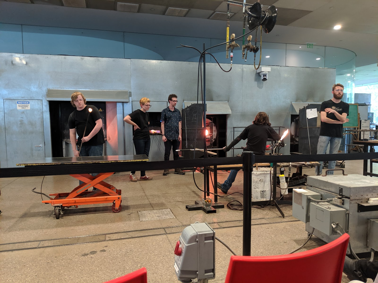 A group of people blowing glass at the hot shop in Toledo.