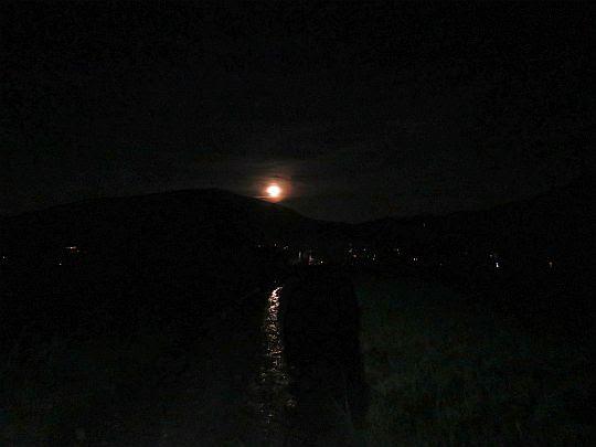 Światełka wsi i blask księżyca rozświetlający drogę.