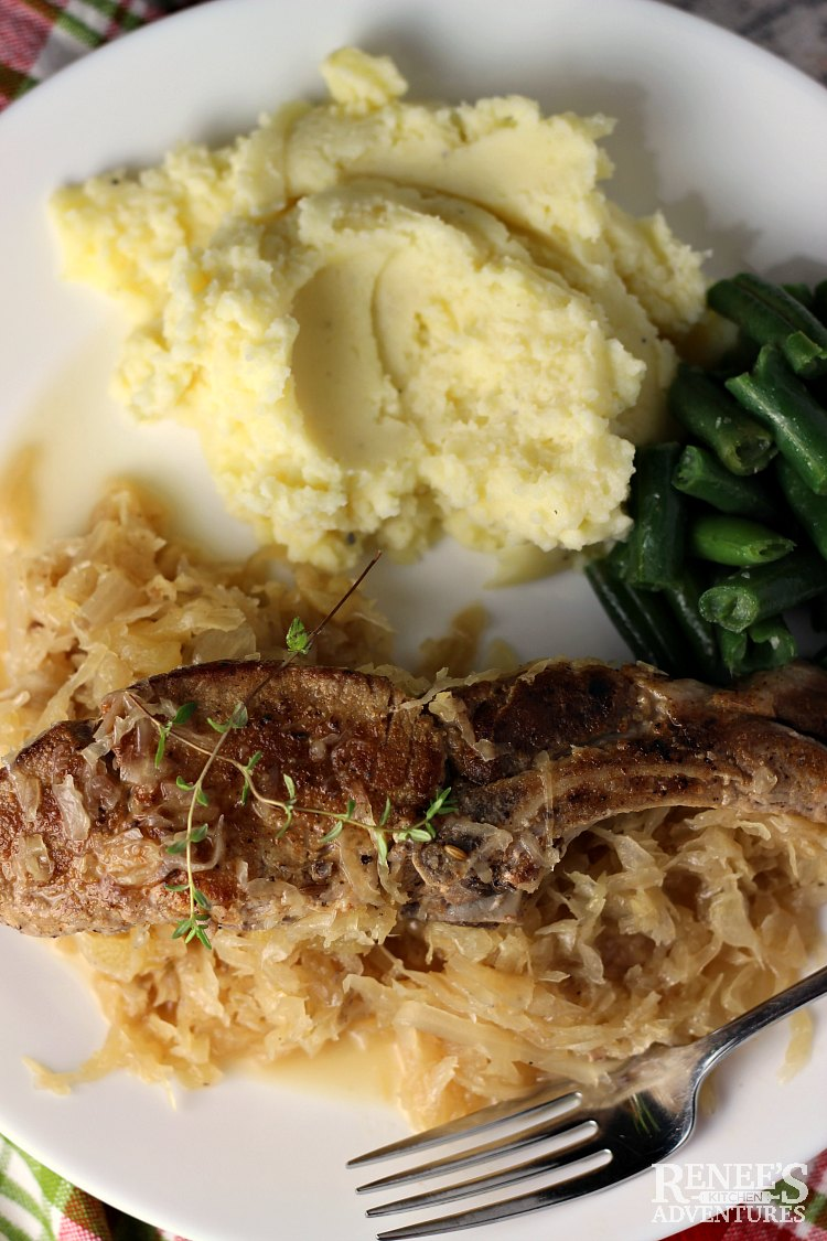 Overhead view of one serving of Country Style Ribs with Sauerkraut by Renee's Kitchen Adventures with mashed potatoes and green beans on a white plate