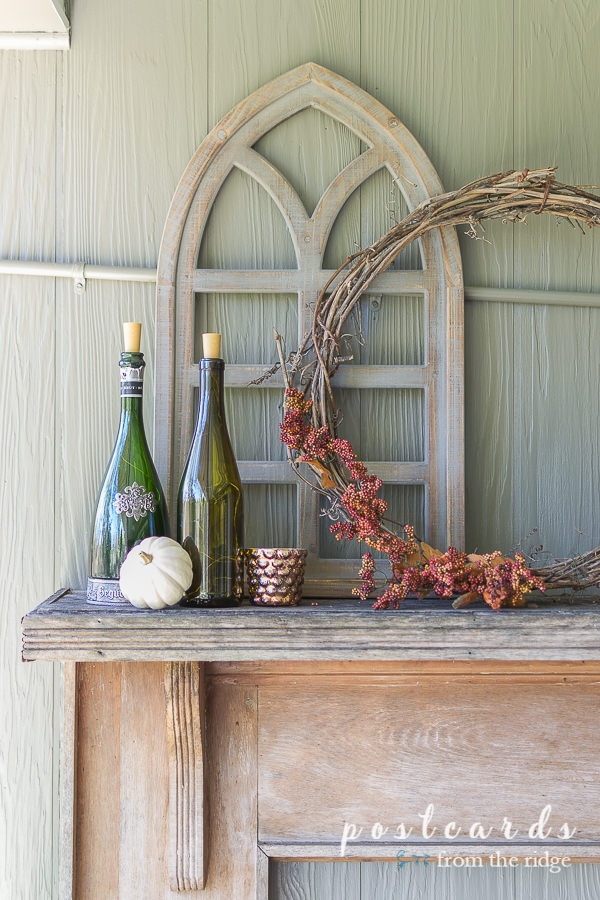 wood cathedral window and wine bottles on vintage rustic mantle