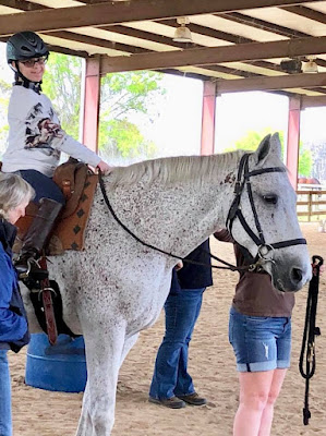 Bryanna is seated atop a white horse with grey spots. She is smiling and looking down at the camera.
