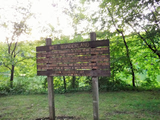 "A wooden sign with golden letters provides information about the ""wet wonderland"" at Bacon Creek Park"