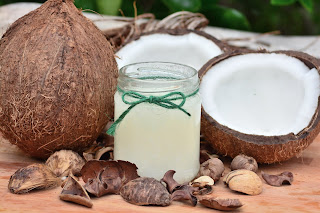 Open coconuts with coconut milk in a jar