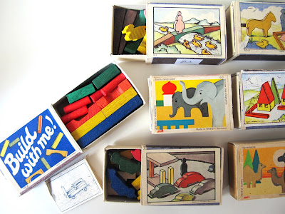 Seven sets of miniature vintage wooden blocks packaged in matchboxes, with one matchbox (with 'build with me' printed on the lid) open to show tiny blocks and an instruction sheet.