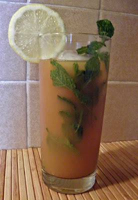 Glass of iced tea garnished with lemon and mint