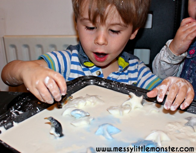 Sensory play and science for kids.  A penguin themed winter small world using frozen oobleck.