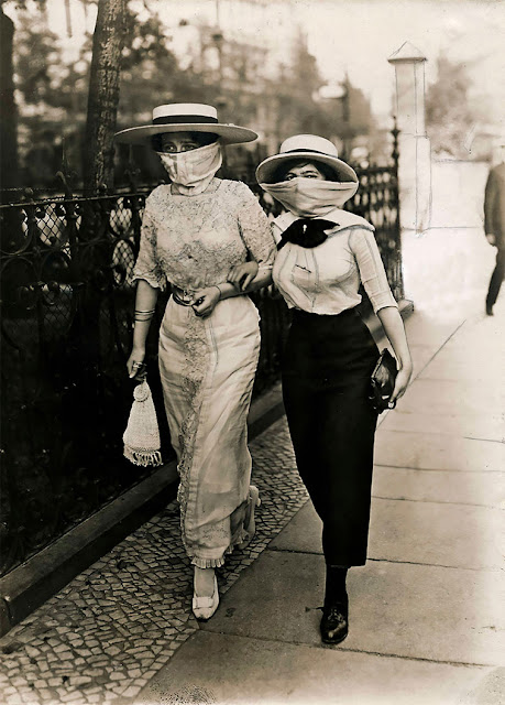 Black and white photograph of two elegant women walking arm in arm with masks during the Spanish flu epidemic