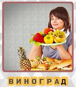 девушка держит поднос с фруктами на котором в том числе лежат гроздья винограда