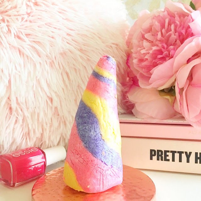 Lush Unicorn Horn Bubble Bar in the centre, pink Essie nail polish to the left. Pink fluffy pillow in the background on the left hand side, a stack of pink books in the background to the right with flowers on top