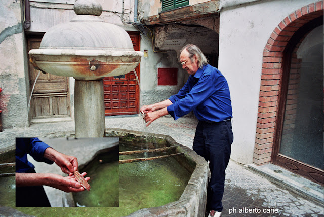 Nico Orengo mentre lava un'acciuga alla fontana di Isolabona