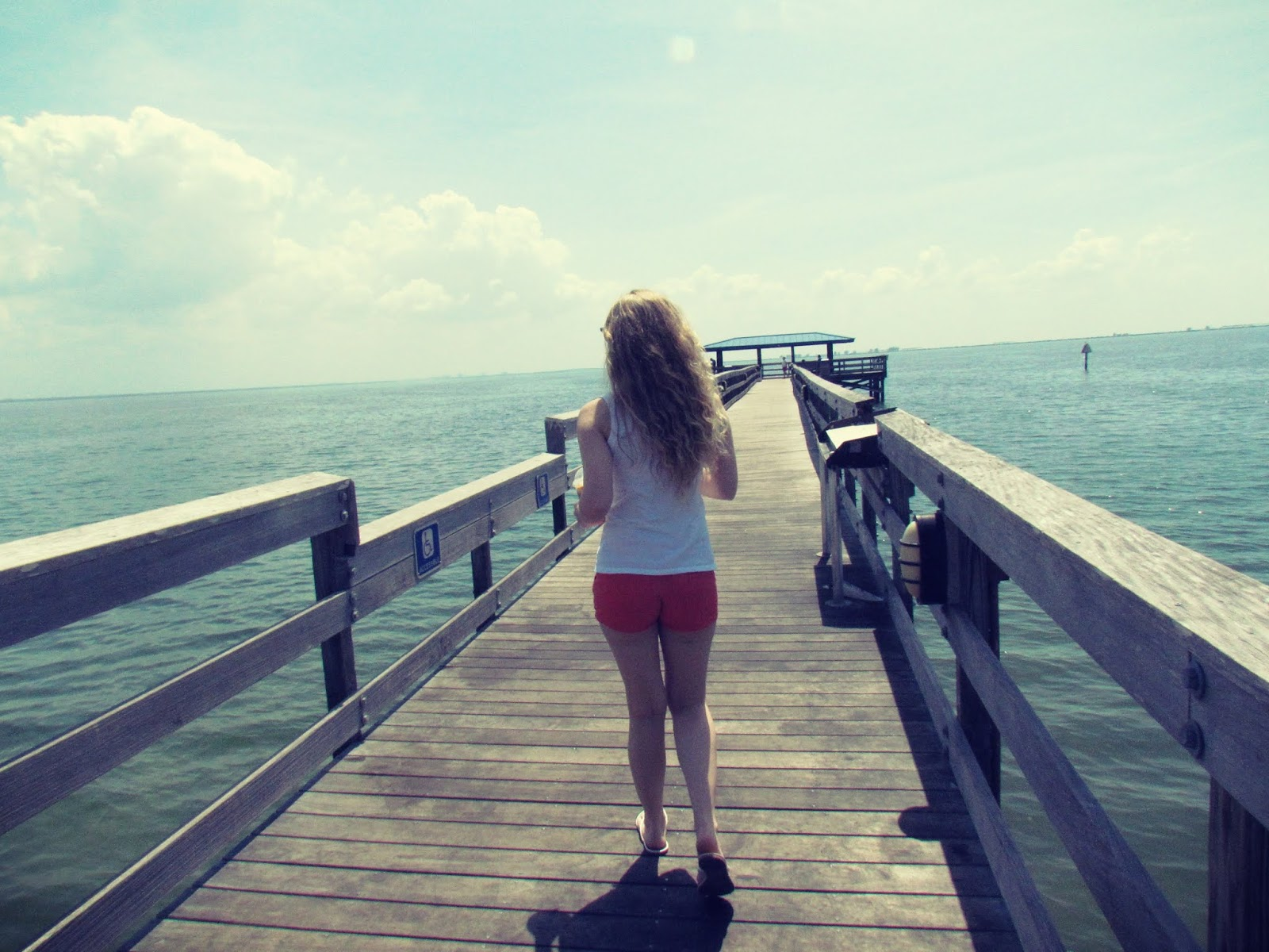 Young blonde woman running down the pier in Safety Harbor, Florida in Orange Shorts