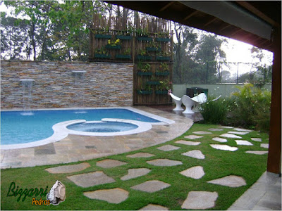 Detalhe da construção da piscina com o piso de pedra Goiás com a parede de pedra, atrás da piscina, com pedra filete de Goiás com execução da cascata da piscina com os caminhos de pedra Goiás e execução da treliça de madeira com eucalipto tratado e a execução do paisagismo.