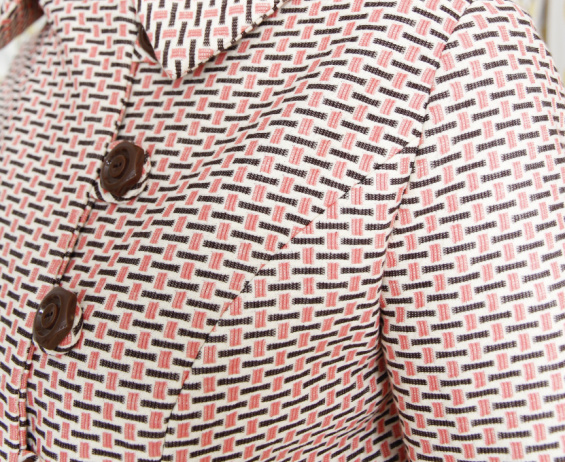a close up picture of a shoulder and buttons of a jacket