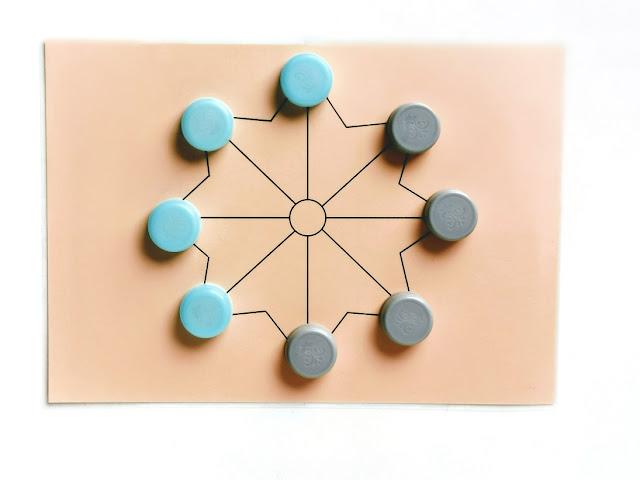 na zdjęciu plansza wydrukowana i zalaminowana a na niej osiem pionków w dwóch kolorach w ustawieniu początkowym