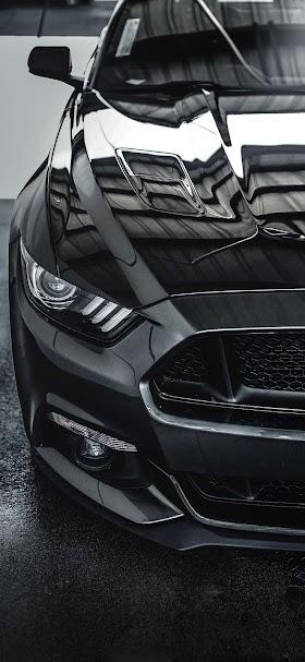 خلفية مقدمة سيارة موستنج سوداء على إسفلت أسود