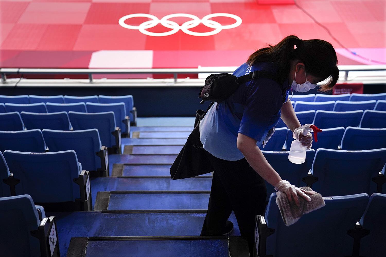Một nhân viên đang khử trùng ghế ngồi trước các trận đấu Judo tại Thế vận hội mùa hè 2020. Ảnh chụp vào ngày 24 tháng 7 năm 2021, ở Tokyo, Nhật Bản, của Jae C. Hong/AP.