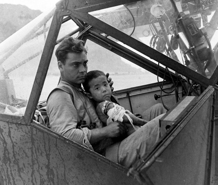 #15 An American Soldier Cradles A Wounded Japanese Boy And Shelters Him From The Rain In The Cockpit Of An Airplane During The Battle Of Saipan While Waiting To Transport The Youngster To A Field Hospital. July, 1944