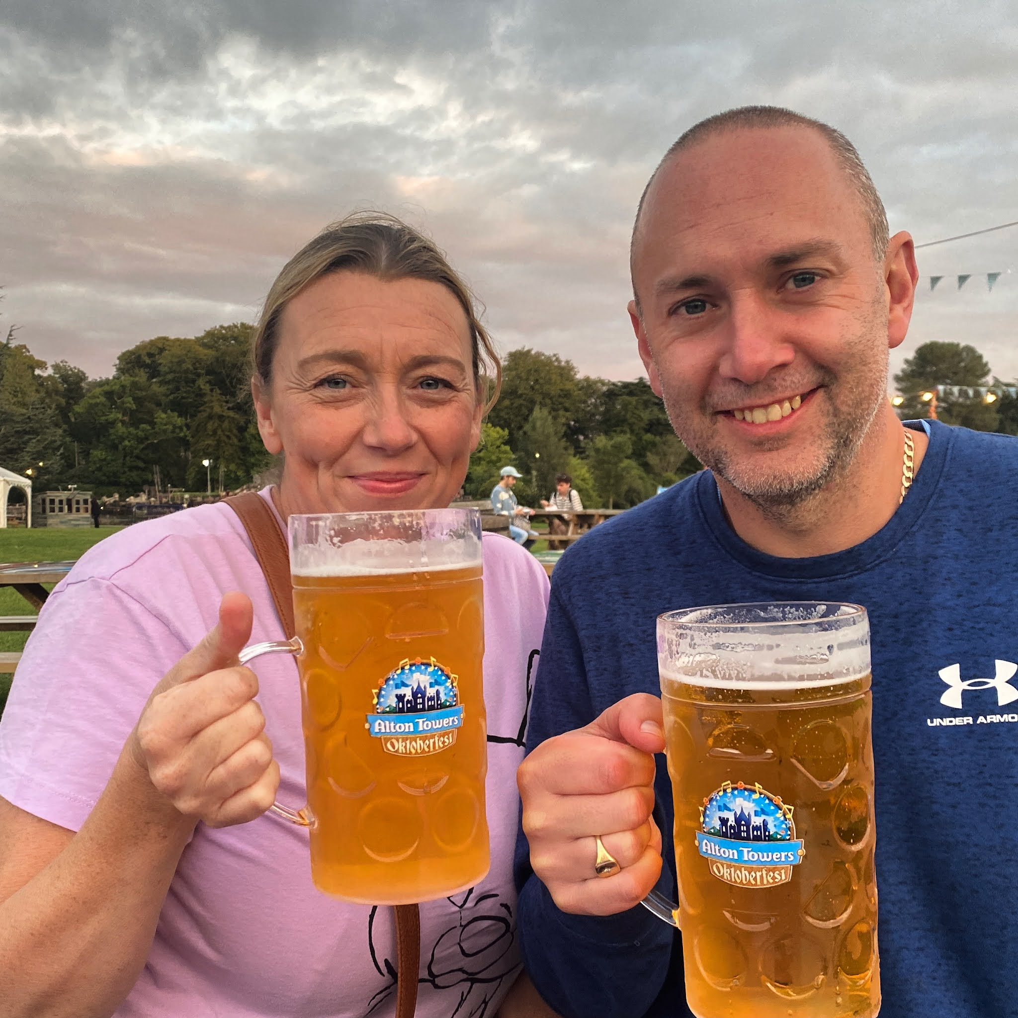 man and woman having a stein of lager