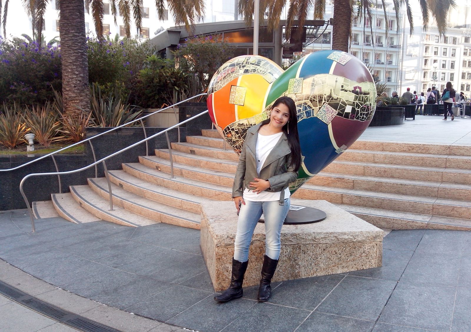 mulher jovem com escultura de coração no meio de uma praça