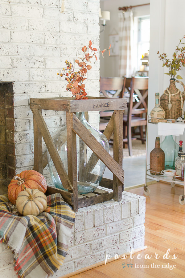 large blue glass bottle in wooden crate, plaid blanket scarf with faux pumpkins, on a painted brick hearth