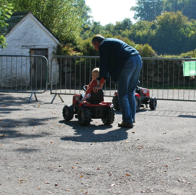 child on tractor with adult pushing