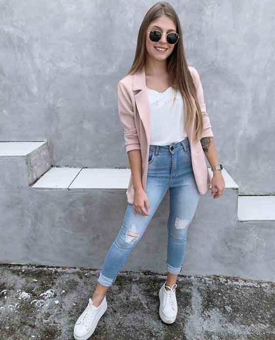 Calça jeans, blusa branca, blazer rosa e tênis