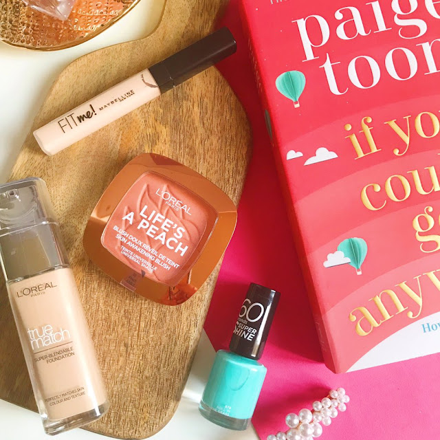 flatlay - concealer, blush, foundation and nail polish on wooden chopping board. Book to the right