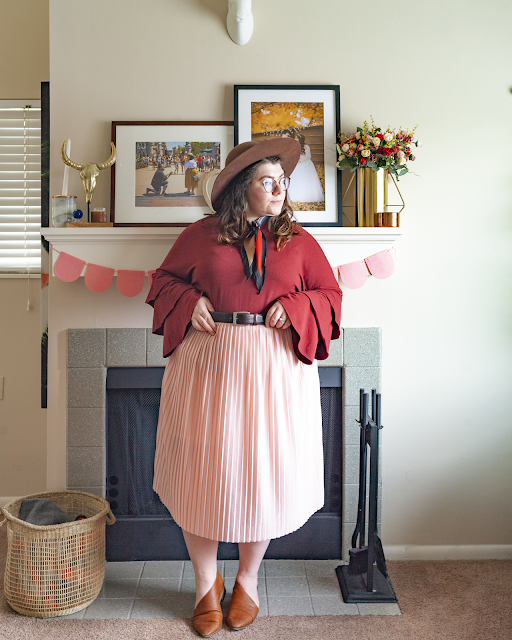 An outfit consisting of a brown wide brim hat, a rust red tri tiered sleeve top tucked into a pink pleated midi skirt and brown d'orsay flats.