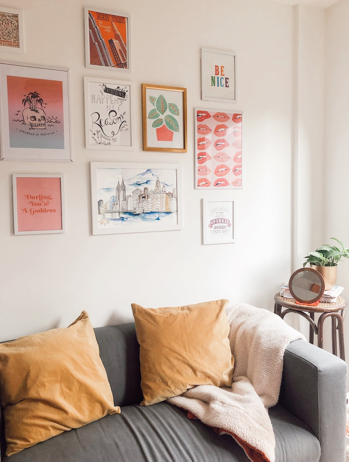 gallery wall featuring mismatched colourful prints above grey couch with mustard velvet cushions and rattan side table with houseplant