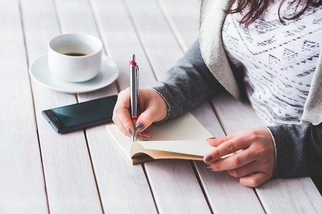 wanita yang memegang pena untuk menulis pada buku