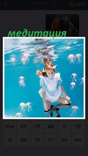 происходит медитация под водой девушкой, вокруг медузы