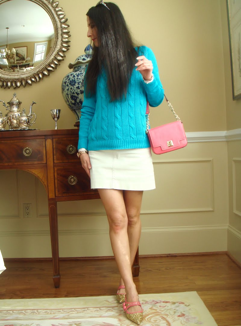 Wearing blue sweater, cream mini skirt, gold glitter shoes with pink trim, and a pink purse and sunglasses.