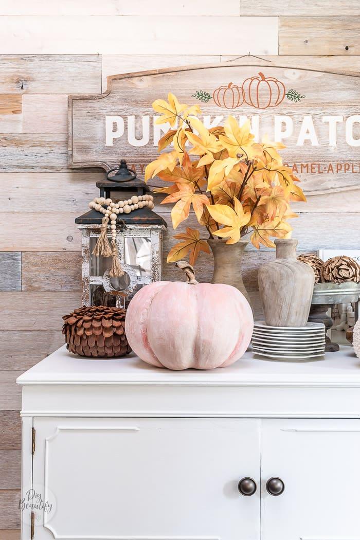 soft orange pumpkin on white dresser with lantern, wood beads, ironstone and fall decor