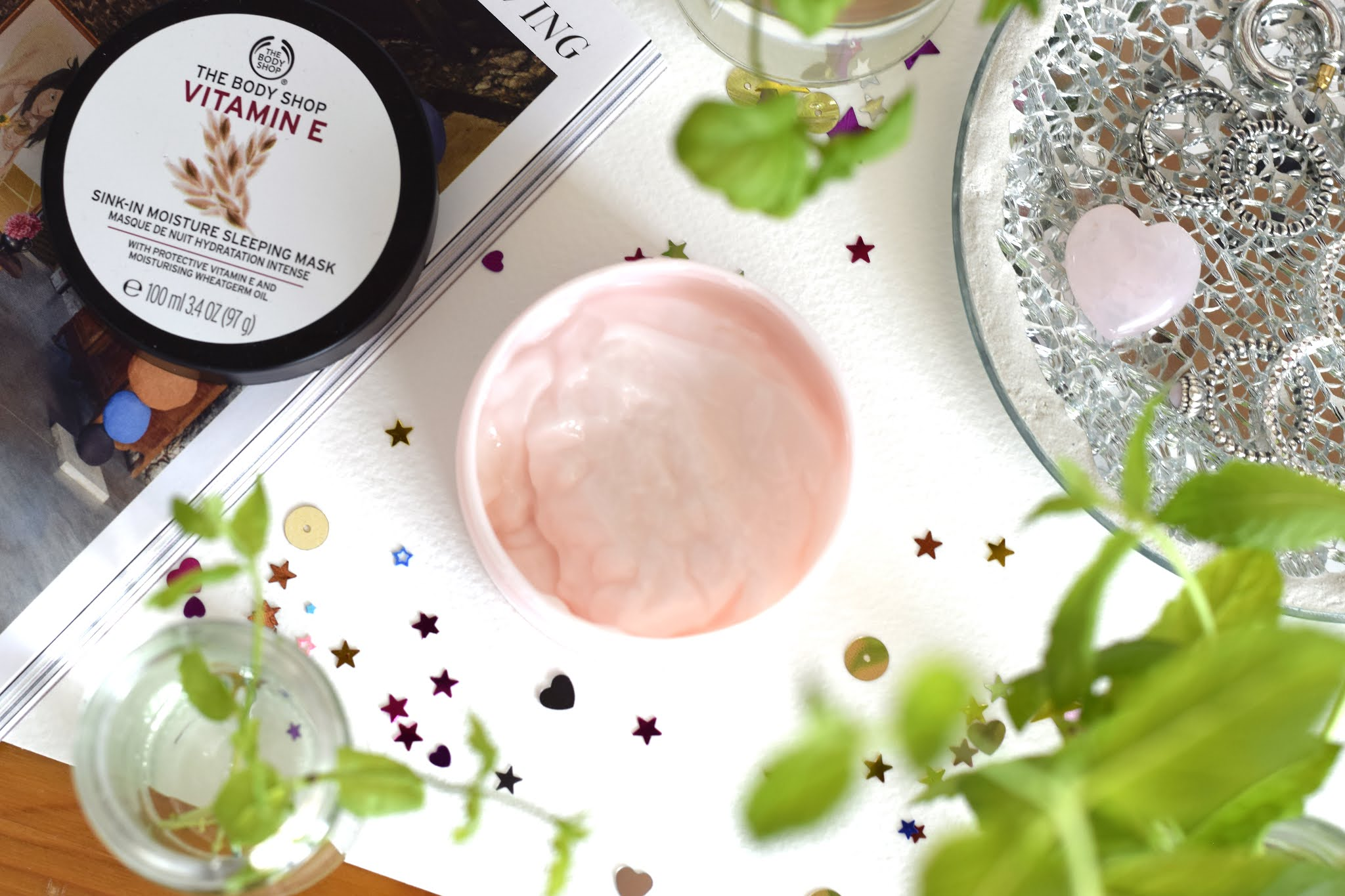 a pot of moisturiser in the center of the image with the lif placed to the side. The pot is surrounded by sequins and jars of mint