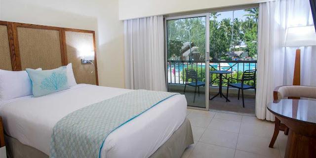 Chambre avec lit double place et balcon avec vue sur jardin et piscine