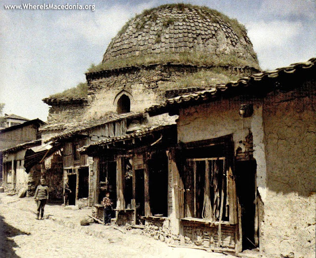 Perspective on an alley on the left of the entrance of Kursumli-an, with a hammam now in ruins. The alley is paved with stones. The shops are leaned against the walls of the hammam. They are built in raw bricks. The photograph shows the shops of a tinsmith and a tailer. In the background, we can see the south-east side of Hammam Gurciler.The Hammam Gurciler (also known as Sengul) was built in the second half of the 15th century and formed an ensemble with the Kursumli-an (on its south-west side) and the Kazandjiler Mosque. It was Musledin Hodja who had it built. It served as a hammam until the great fire of 1689. It was known as kuri-hammam (dry bath). The 1963 earthquake destroyed it completely. The hammam is characteristic of Islamic buildings. Its cupola is covered with tiles. Today, this space is part of the courtyard of the Macedonian Museum.