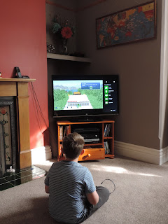 boy playing minecraft on x-box console