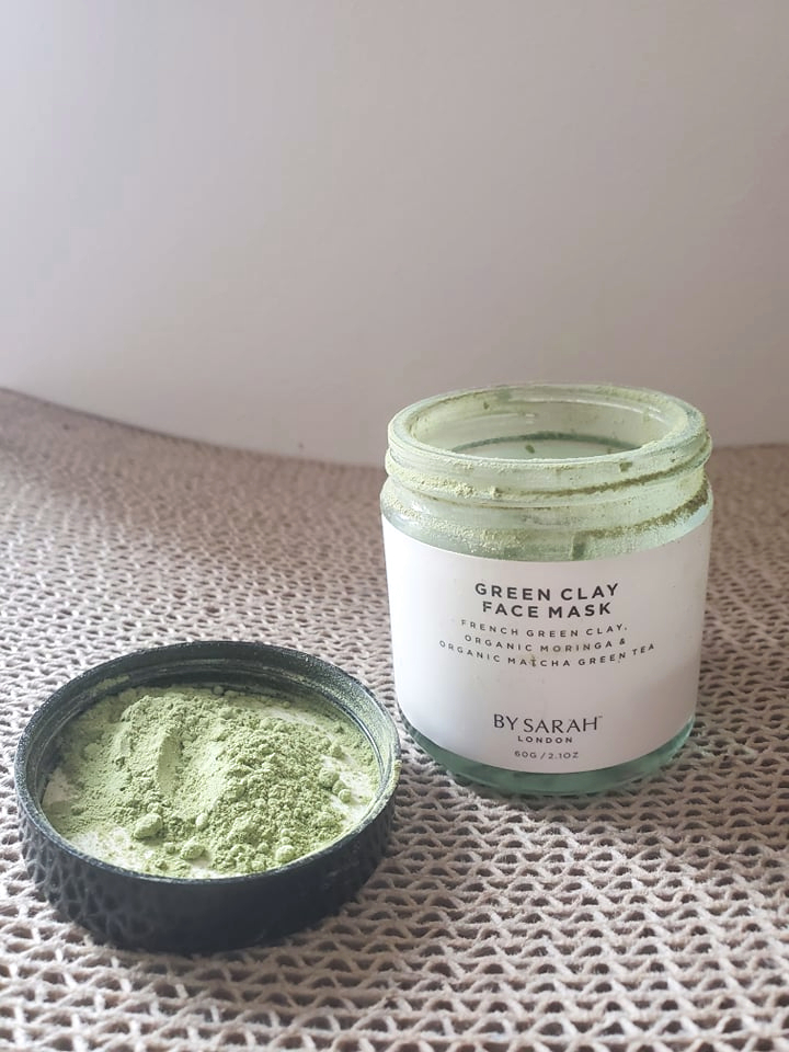 green clay face mask from By Sarah London with vivid green powder next the the jar